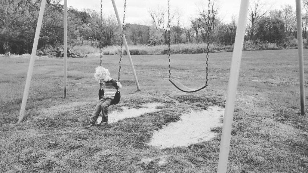 boy swinging alone