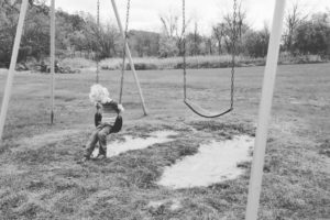 boy swinging alone