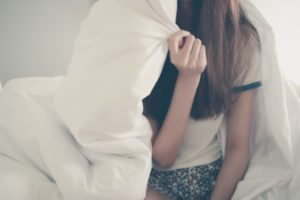 Happiness of young Asian woman lying with blanket on bed in the morning. Winter day. Copy space. Vintage effect style pictures.
