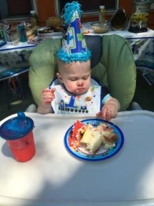 Child Eating Cake on First Birthday
