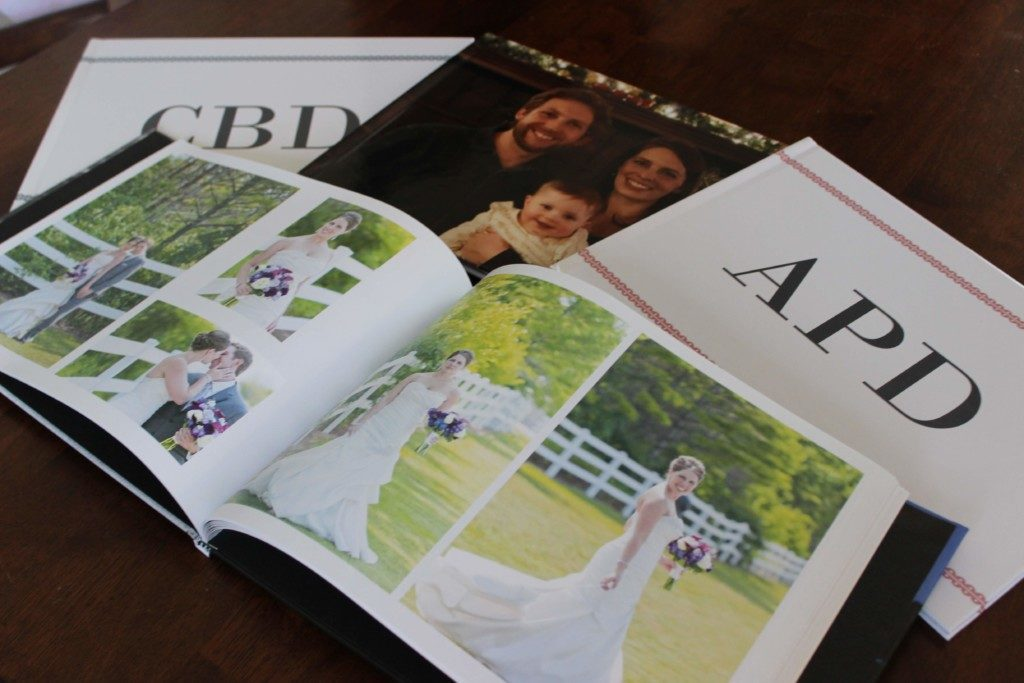 a pile of four photo books with one open to wedding pictures