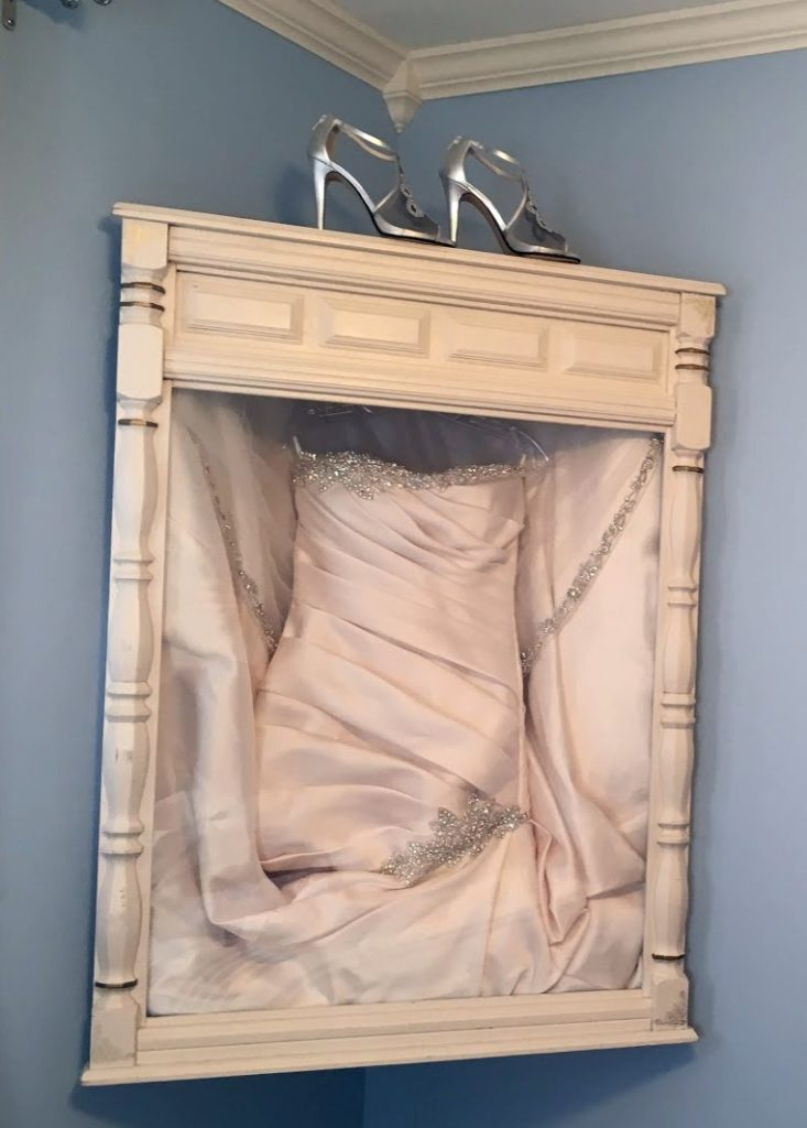 corner shadow box displaying a wedding dress with shoes on top