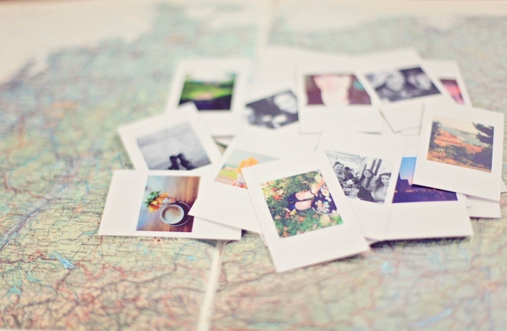 a pile of photos on top of a map