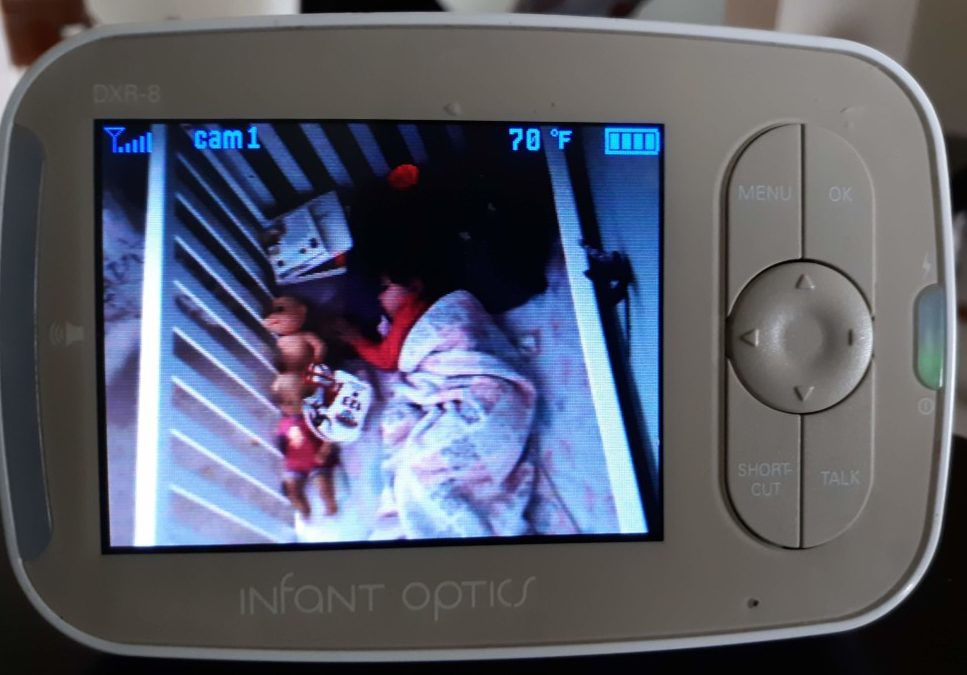 baby monitor showing toddler sleeping in crib with many items