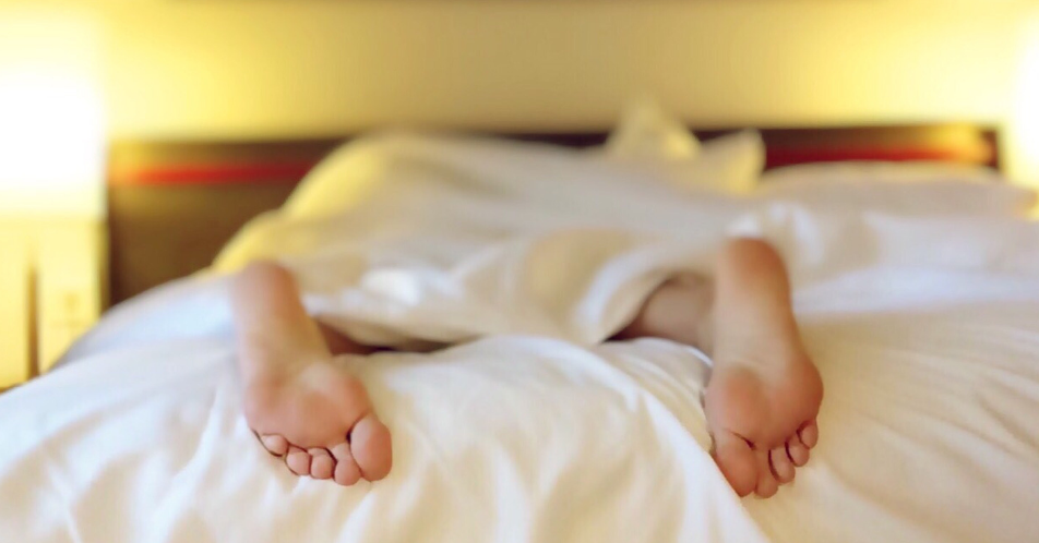 woman laying down on bed with feet sticking out of covers