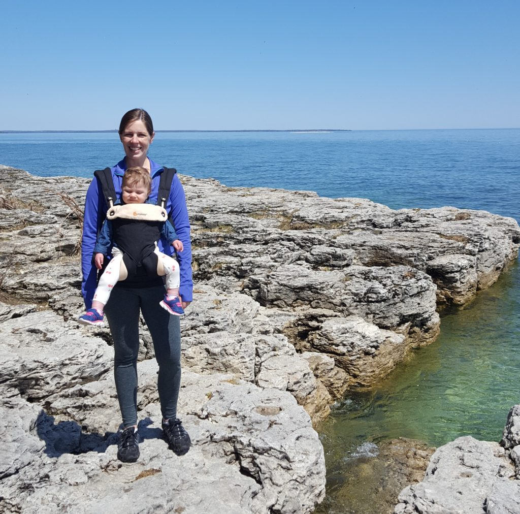woman with baby in carrier hiking on rocks next to water