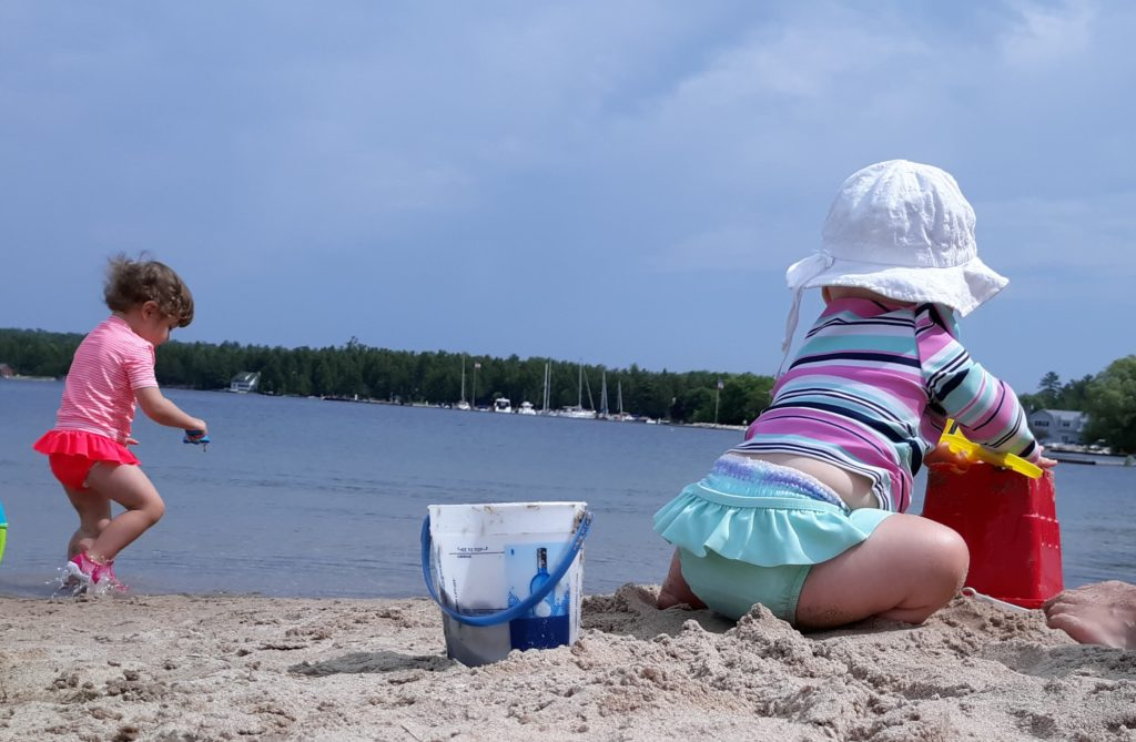 toddler and baby at sand beach