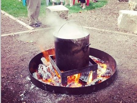 huge pot of boiling fish over fire