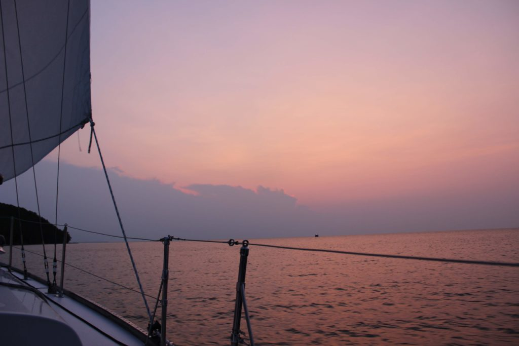 View of sunset from edge of sailboat