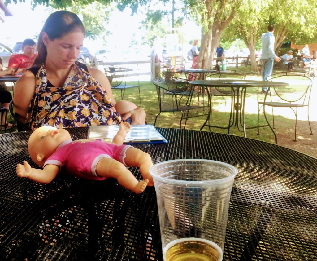 Woman nursing baby outside at a table