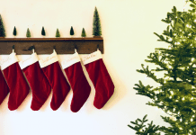 Six red stockings hung from shelf