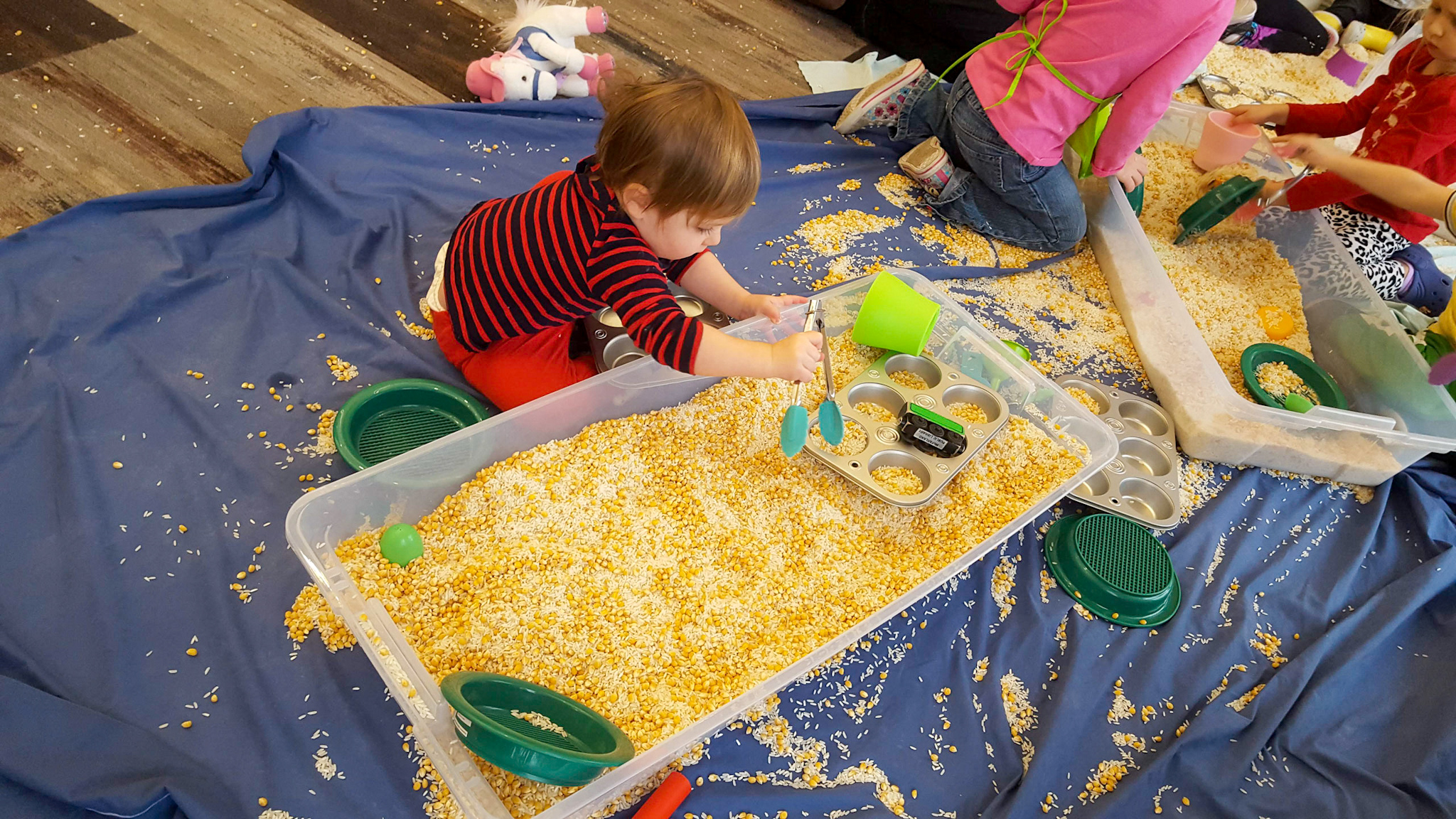 toddler playing in corn sensory bin