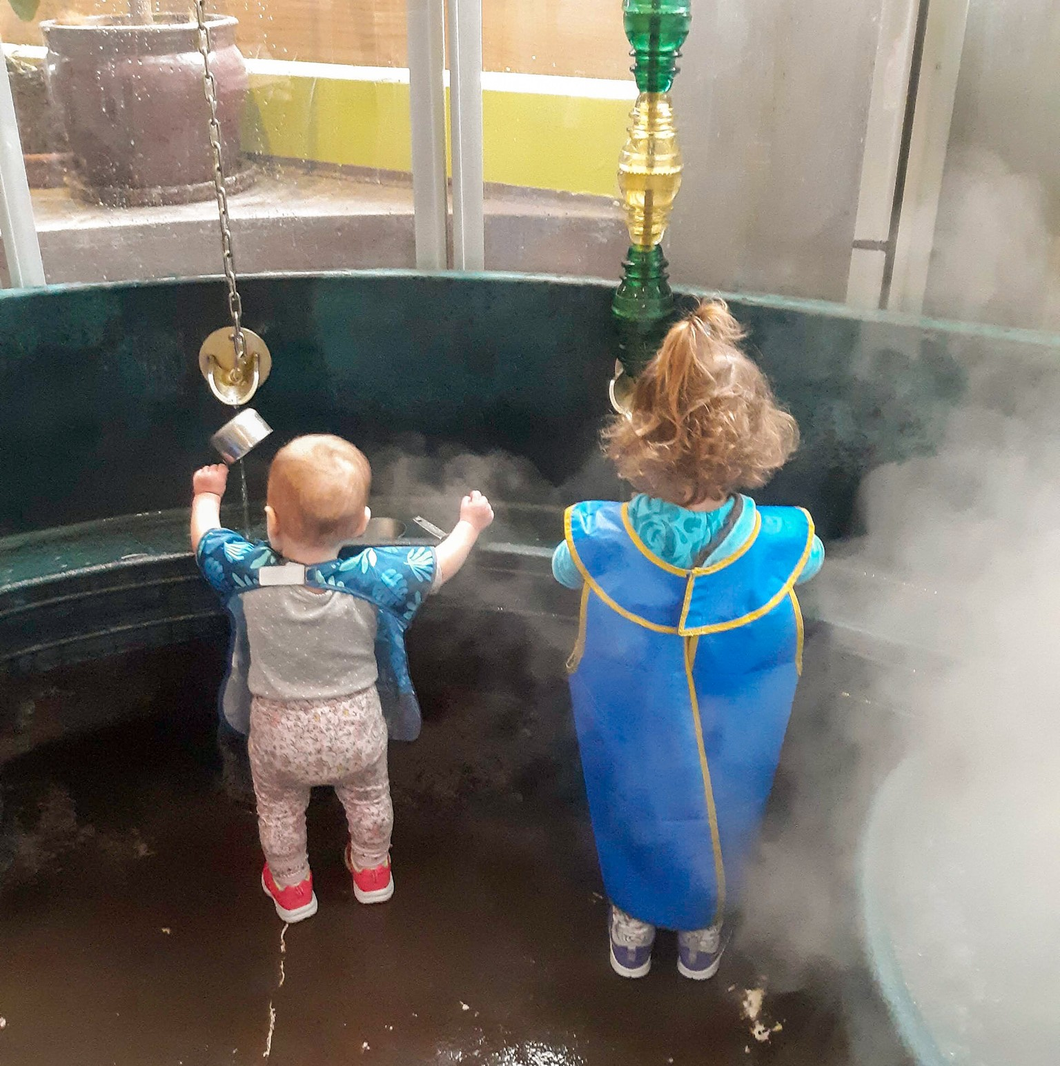 two toddlers playing in a water feature