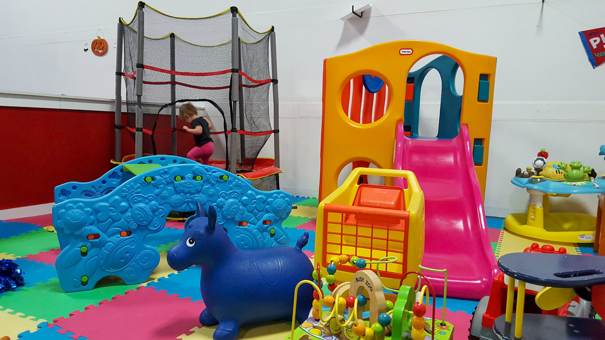 toddler jumping on trampoline in play area