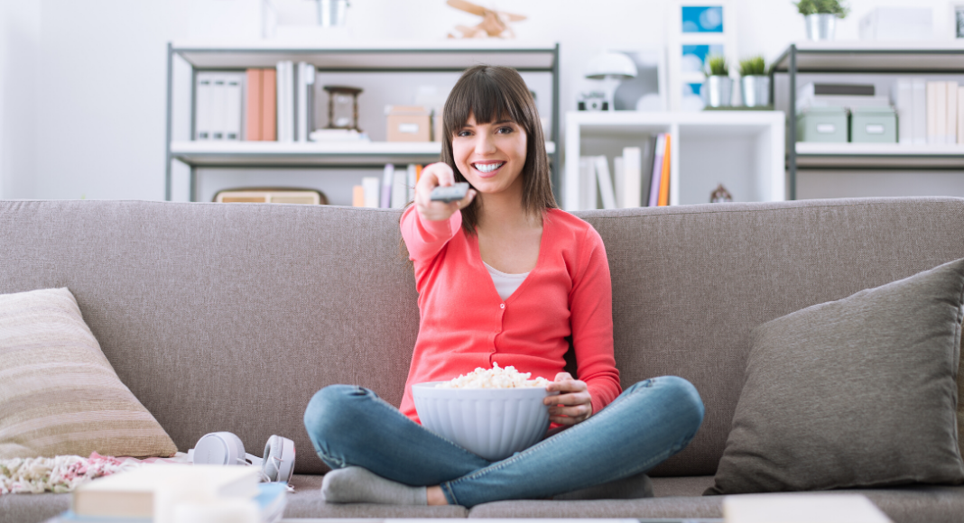 woman holding remote while sitting on a couch with popcorn in her lap