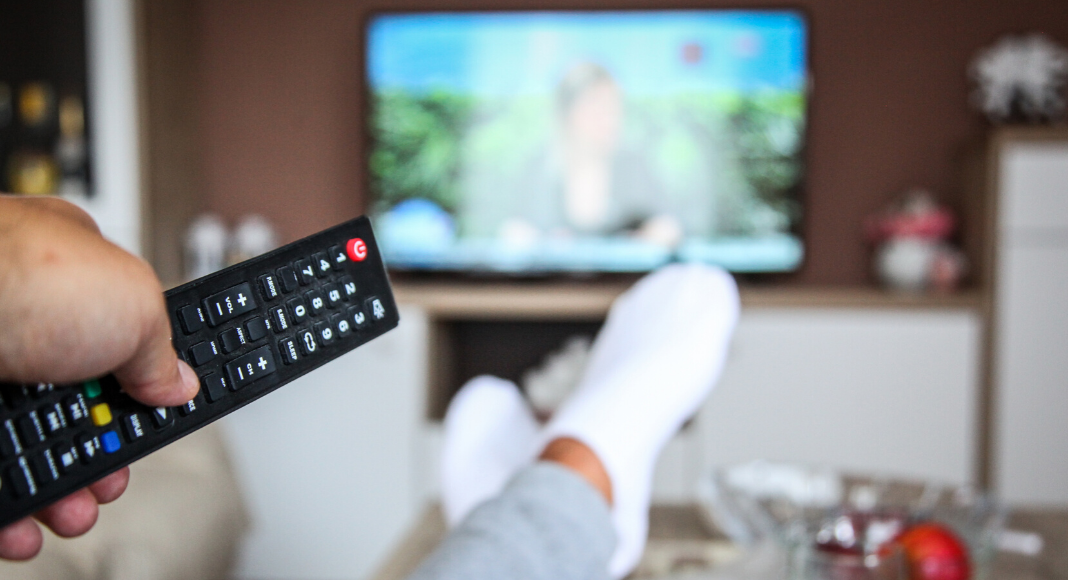 person watching tv holding remote with feet propped up on coffee table