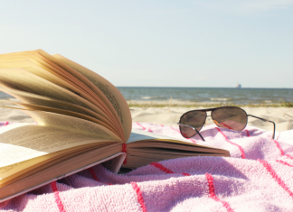 open book on beach towel next to sunglasses